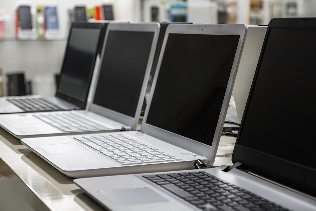 Plusieurs ordinateurs portables alignés sur le présentoir d'un magasin
